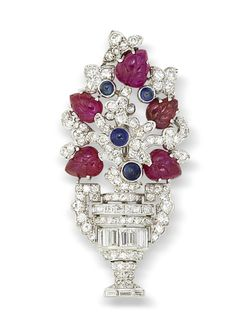 An art deco sapphire, carved ruby and diamond brooch, by Lacloche Frères, circa 1925  The single, baguette and step-cut diamond urn issuing a stylised floral stem set with single-cut diamonds and highlighted with carved ruby leaves and cabochon sapphire bud detail, diamonds approximately 3.00 carats total, signed Lacloche Paris, numbered, height 5.0cm