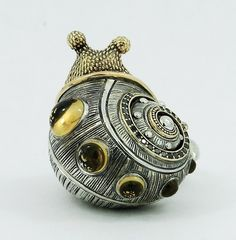 Sergey Zhiboedov: handcarved ring composed of 5 separate pieces in Sterling Silver and 14k yellow Gold. The intricate carvings were done by hand and the snail is also adorned with 6 Citrine cabochons, and .25ctw of black diamonds