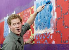 Prince Harry has a go at some local artwork during a trip to the Atlantic Rainforest on June 25, 2014 near Sao Paulo, Brazil.