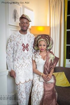 Brown and white traditional Nigerian wedding attire. Bride in brown and gold gele. Groom in brown and white. Lace aso ebi.   Photography by Abi.