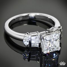 This Custom Diamond Engagement Ring is set in Platinum and holds 2 Marquise and 4 Bagguettes. The 4 prong head features v-tips and holds a beautiful 1.76ct Princess Cut Diamond.