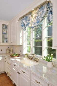 .Love the countertop! Tulips! Sun coming through the window. Nice blue touches..