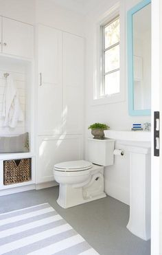 Bathroom and mudroom combo features a turquoise mirror over a pedestal sink next to an under window toilet alongside a white and gray stripe rug layered atop a gray penny tiled floor.