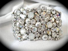 I make this stunning rhinestone cuff bracelet from top quality Swarovski crystal rhinestones and crystal pearls. It features a variety of stones in clear crystal, crystal AB, white opal and Swarovski crystal pearls for maximum sparkle and bling. I...