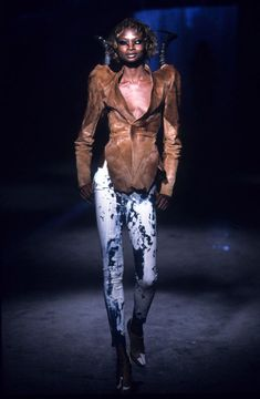 Alexander McQueen -   Ensemble:   It's a Jungle Out There, autumn/winter 1997–98.   Jacket of brown pony skin with impala horns; trousers of bleached denim.