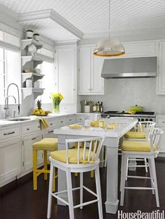 Easy way to add color - stool cushions and tea towels. Silver and yellow kitchen by designer Christina Murphy.  #kitchen