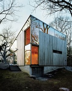 """Guilford Cottage  Sheets of unframed glass fill the spaces between the building's operable windows and the sloping eave of the roof, giving the house, as architect Alan Organschi puts it, """"the feel of coming apart at the seams—of surfaces unhinged."""""""