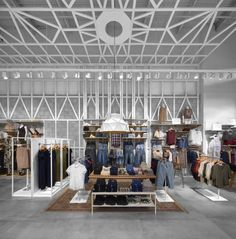 The store holds both men and women's collections, so a dividing display wardrobe was placed in the center of the store, but in order to maintain the dramatic effect of the ceiling pattern we kept the wardrobe height low so the pattern in continuous from one side of the store to the other.