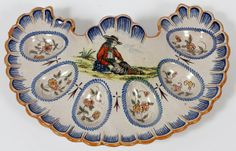 """QUIMPER POTTERY EGG TRAY, 19TH C., W 10'':Having scalloped edges. Decorated with amber rims, enhanced by inner blue lines. Featuring a scene of seated man on a landscape at the center. Measures W.10"""" x 8""""."""