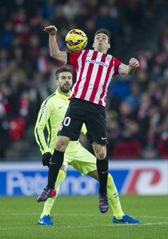 Lionel Messi of FC Barcelona duels for the ball with Aritz Aduriz of Athletic Club during the La Liga match between Athletic Club and FC Barcelona at San Mames Stadium on February 8, 2015 in Bilbao, Spain.