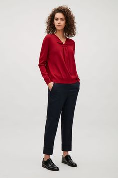 Designed with a drape detail, this top has a simple slit at the front that fold over to form a neat collar. Made from a fine knitted material, it is completed with long sleeves and tightly ribbed finishes.