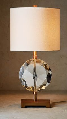 Inspired by an intricately faceted diamond, our Bijoux Table Lamp brings elegant illumination to your home's decor. The cut crystal body sits atop a brass base and is paired with a white linen shade.