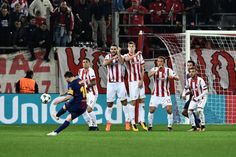 Barcelona's Argentinian forward Lionel Messi (L) kicks the ball in front of Olympiakos players during the UEFA Champions League group D football match between FC Barcelona and Olympiakos FC at the Karaiskakis stadium in Piraeus near Athens on October 31, 2017.  / AFP PHOTO / ARIS MESSINIS - 64 of 90