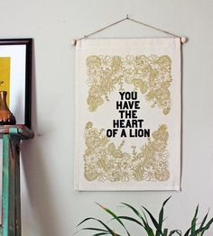 "The simplest of words are oftentimes the most meaningful, and that's certainly the case when it comes to this lovely wall banner. The canvas banner is printed with ""You Have The Heart Of The Lion"", surrounded by a whole bunch of metallic gold succulent blooms. Hang it somewhere you'll see (and consequently smile) often."