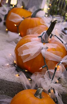 soften the pumpkin-esque decor...a little tulle & twinkle lights...eery ambiance uniquely displayed