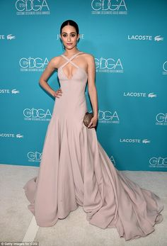 Hostess with the mostess: Emmy Rossum stood out in off-white at the 17th Costume Designers Guild Awards in Beverly Hills, California, on Tuesday night