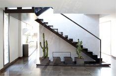 Escalier sur limon central en métal dans un intérieur épuré résolument contemporain. Marches en tôle lisse pliée formant contremarches. Finition acier brut patiné. Fabrication française. Escaliers Décors®.