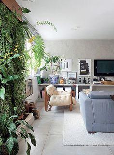 A falta de varanda poderia ser um impedimento para o apartamento do paisagista Gil Fialho. Mas ele encontrou uma solução para ter plantas na área interna: um jardim vertical entre as janelas da sala. Há samambaias, bromélias e orquídeas
