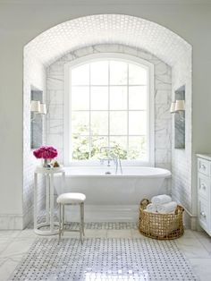 Designer Mark Williams makes the slipper tub the star of this luxurious bathroom by tucking it into a tile-covered arch beneath an oversized Palladian window. Larger 9 x 18 Carrara marble tiles surround the window while smaller marble subway tiles line the arch. To complete the traditional look, Mark chose Cararra marble and black granite basketweave tiles for the bathroom's floor. by blanca