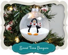 Stenciled penguin on a snow-filled Christmas ornament is a fun addition to the kids' tree. #Holiday