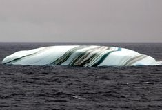 Icebergs in the Antarctic area sometimes have stripes, formed by layers of snow that react to different conditions. Blue stripes are often created when a crevice in the ice sheet fills up with meltwater and freezes so quickly that no bubbles form. When an iceberg falls into the sea, a layer of salty seawater can freeze to the underside. If this is rich in algae, it can form a green stripe. Brown, black and yellow lines are caused by sediment, picked up when the ice sheet grinds downhill towar...