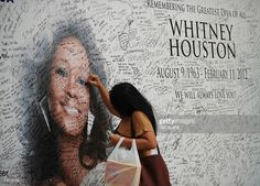 A Fillipino fan of US pop diva, Whitney Houston, signs a tribute mural displaying a portrait of her idol at a mall in Manila on February 17, 2012. Houston, who died on February 11 aged 48 in a Beverly Hills hotel, will be laid to rest on February 18, after a private funeral service at the New Jersey Baptist church where she grew up singing in a gospel choir.