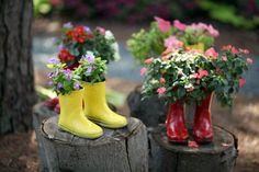 Die Paare der gelben und roten Gummistiefel stehend auf einem segmentierten Baumstamm verleiht eine künstlerische Ambiente. Die bunten Gummistiefel Pflanzgefäße bieten spielerischen Kontrast zu den bunten Blumen Pflanzen und ihre üppigen grünen Blättern.