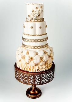 Four-tiered ivory cake inspired by a wedding gown with a billowing bottom tier, gold banding and button details. Whimsical Wedding Cakes, Milton, ON, Canada... the bottom layer reminds me of a plushy, soft quilt!