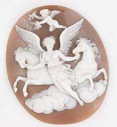 An unmounted oval shell cameo Carved to depict the winged goddess Eos leading two horses over clouds, accompanied by a cherub scattering flowers, length 5.3cm.