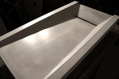 Asymmetric Concrete Ramp Sink with integral slot drain by www.formastudios.co.uk