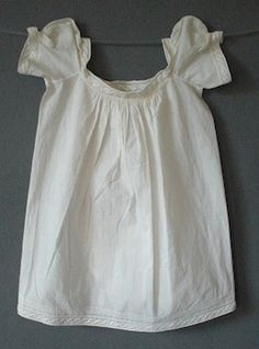 Baby Dress  c 1810  of white cotton with slight raised embroidered border in a spot and interlocking meander design, fine pleating, the small puff sleeves with embroidered overlapping detail, one neck drawstring to front and two to back, the back with two Dorset buttons at either side of the square neckline and a curved overlap opening all with embroidered edging and fine pleats, 18 in or 46 cm long.  Meg Andrews