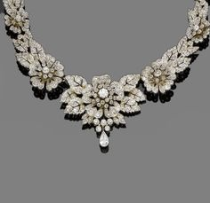 Diamond Necklace / Tiara combination, circa 1890. Composed of graduating pierced flowerheads and leaves, the largest to the centre, set throughout with diamonds, with a pear-shaped diamond drop, mounted in silver and gold. Brooch fitting provided for central piece, fitted case.