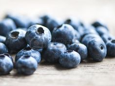 blueberries rustic table: Blueberries on wooden table; focus on single blueberry Shallow DOF