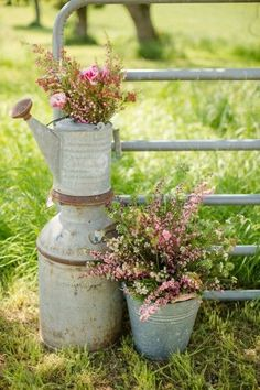 vignette of old watering cans and farm pails, adorned with flowers / http://www.deerpearlflowers.com/rustic-country-milk-jug-wedding-ideas/