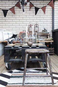 Eieren har holdt dekoren på denne uteplassen i en nøytral fargepallett, som friskes opp av rødt og rustrødt. Gamle flasker er fine lysestaker, hageleker er fin pynt når de ikke er i bruk. Den røde retrovifte er fra et loppemarked, mens den lille keramikk-kannen er arvet. Boldet er laget av en pall som har fått hjul og et strøk beis.