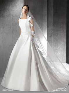 Princess wedding dress in mikado. Bodice with bateau neckline and draped sash. Plunging V-back. Skirt in mikado silk with pleats at the sides.