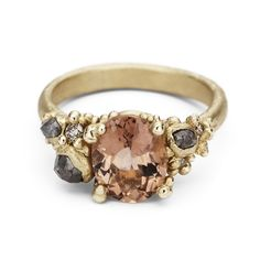 Description A soft coloured peachy-pink tourmaline set amongst rose cut grey diamonds, champagne diamonds and granules of yellow gold on a gently textured band