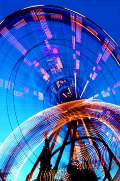 These two whirling, twirling amusement park rides adjacent to one another are making radiant circles of light as dusk falls at a local theme park near Salt Lake City, Utah, USA. You can imagine the dizzying fun the riders must be having.