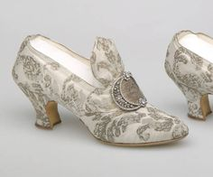 1910 Pumps of gray silk satin and metallic brocade. Pointed toe; ornamental oversized tongue; rhinestone and metallic thread buckle attached to vamp; buckle resembles two crescent moons attached at their pointed ends; self-fabric baby French heel. F. Pinet, designer.