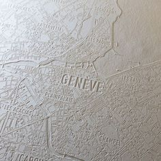 An engraved paper map of Geneva Switzerland.  Located at Lac Léman (Lake Geneva) this is the second largest city in Switzerland. Headquarters of Europes United Nations and the Red Cross  Geneva is a global hub for diplomacy and banking.  This laser engraving shows the streets waterways and names of the neighborhoods. Made in Zurich Switzerland.  #map #maps #geneva #geneve #genève #visitgeneva #switzerland  #paper #paperart #engraving #lasercut #laserengraved #swissmade #swissdesign… Switzerland Cities, Geneva Switzerland, Open Street Map, Swiss Design, Lake Geneva, United Nations, Red Cross, Zurich, Laser Engraving