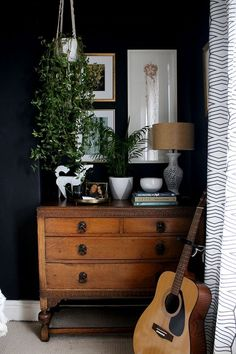 vintage chest of drawers with plants look great against a black panted wall