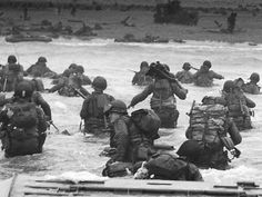 An LCVP disembarks troops of Company E 16th Infantry 1st Infantry Division (the Big Red One) wading onto the Fox Green section of Omaha Beach on the morning of June 6 1944. American soldiers encountered German 352nd Division when landing. During the initial landing two-thirds of the Company E became casualties.
