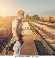 Young Caucasian blond hipster man with backpack waiting for train at a station. Trendy casual guy standing looking away, unrecognizable person, square format image, filter applied.