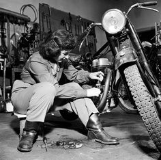32 Badass Vintage Photographs Of Women And Motorcycles A woman repairing her motorbike inside a workshop, 1950.