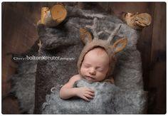Newborn in felted deer bonnet and rustic bed prop