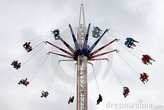 A swing ride in an amusement park with people having fun.
