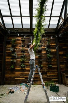 Rebecca of Greenery NYC building a floral garland and hanging cafe lights at Brooklyn Winery for an August wedding. Photo by Kelly Williams Photography.