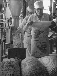 1939 Kansas Wheat Workers filling colorfully printed flour sacks which housewives use to make dresses because the labels wash out, at Sunbonnet Sue flour mill. - Photo by Margaret Bourke-White