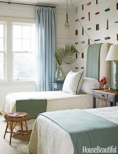 MOUNTED SPOOLS In a Florida guest bedroom, designer Tammy Connor covered twin headboards in Matteo's nubby Knot throws to amp up texture. She also made a graphic pattern on the wall out of vintage spools of thread.