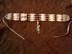 This choker is made from white hairpipe beads and strung together with sinew with silver plated beads and an inlaid silver eagle arrowhead pendant , http://www.nativeamericanstuff.net/American%20Indian%20Chokers%20Breast%20plates,%20Bracelets%20&%20More.htm